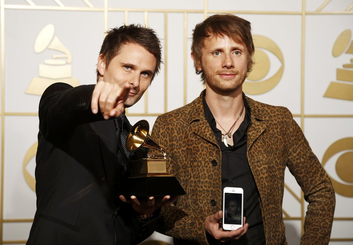 Matt Bellamy (L) and Dominic Howard, of the rock band Muse, hold their award for Best Rock Album for Drones during the 58th Grammy Awards in Los Angeles, California February 15, 2016.  REUTERS/Lucy Nicholson