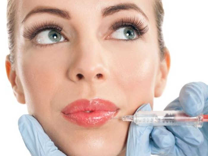 Beautiful woman gets an injection in her lips.