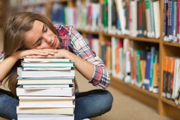 Sleeping student sitting on library floor leaning on pile of books