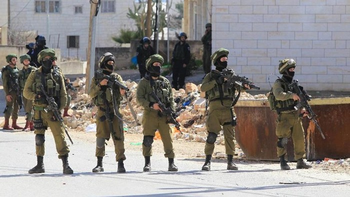 Israeli security forces hold position as Palestinians protest near the Jewish settlement of Kiryat Arba on February 26, 2016 (AFP Photo/Hazem Bader)