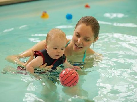 Mother and baby daughter in swimming pool playing with ball