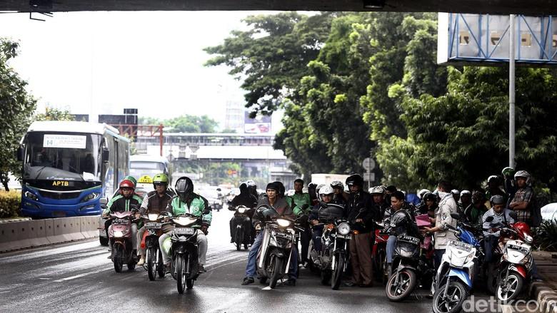 Hujan mengguyur kawasan Senayan, Jakarta, Jumat (4/3/2016) pagi. Hujan membuat banyak pengendara sepeda motor berteduh di kolong jembatan Senayan.