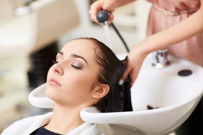 Woman having hair washed in hair salon, elevated view