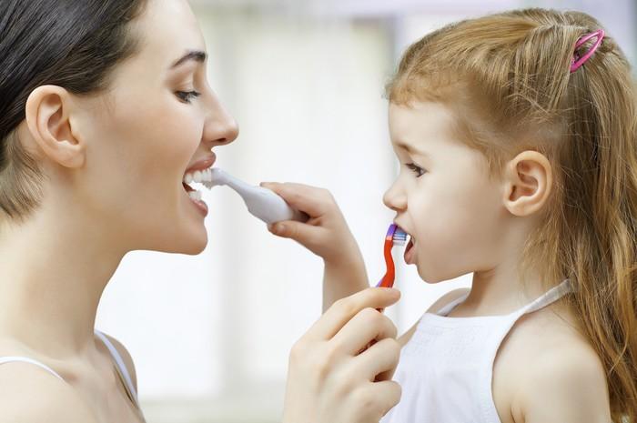 Anak dan ibu saling menggosok gigi