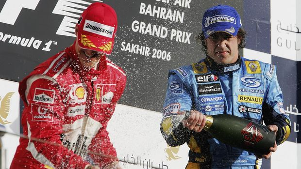 SAKHIR, BAHRAIN - MARCH 12:  Fernando Alonso of Spain and Renault sprays Michael Schumacher with champagne after winning the Bahrain Formula One Grand Prix at the Bahrain International Circuit on March 12, 2006 in Sakhir, Bahrain  (Photo by Clive Mason/Getty Images)