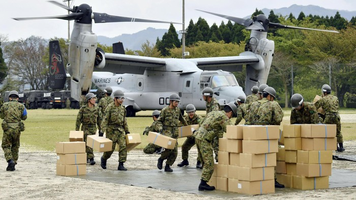 Japan Ground Self-Defense Force soldiers carry aid materials from a U.S. military Osprey aircraft (behind them) after a series of earthquakes, at Hakusui sports park in Minamiaso town, Kumamoto prefecture, southern Japan, in this photo taken by Kyodo April 18, 2016. Mandatory credit REUTERS/Kyodo  ATTENTION EDITORS - FOR EDITORIAL USE ONLY. NOT FOR SALE FOR MARKETING OR ADVERTISING CAMPAIGNS. THIS IMAGE HAS BEEN SUPPLIED BY A THIRD PARTY. IT IS DISTRIBUTED, EXACTLY AS RECEIVED BY REUTERS, AS A SERVICE TO CLIENTS. MANDATORY CREDIT. JAPAN OUT. NO COMMERCIAL OR EDITORIAL SALES IN JAPAN.