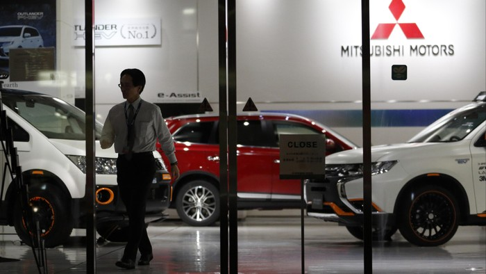 TOKYO, JAPAN - APRIL 20:  An employee  walks past a Mitsubishi Motors vehicles displayed at the companys headquarters on April 20, 2016 in Tokyo, Japan. Mitsubishi Motors share plunged more than 15% after the Japanese car maker announced it has mishandled the fuel economy test data.  (Photo by Tomohiro Ohsumi/Getty Images)