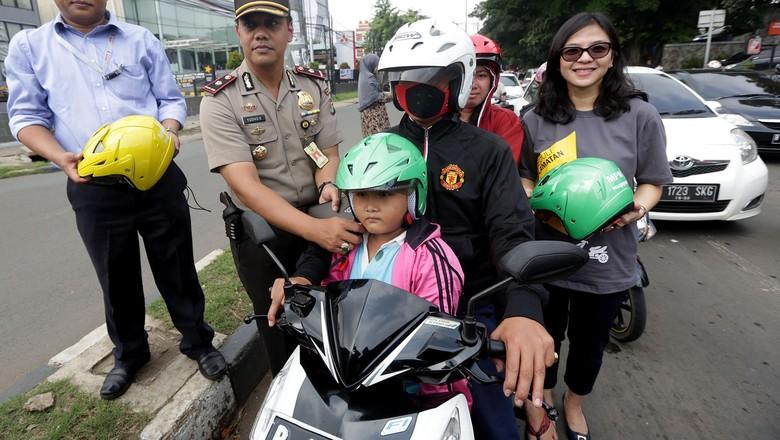 Aksi peduli keselamatan berlalulintas digelar di Duren Sawit, Jakarta Timur, Rabu (24/4). Aksi dilakukan dengan cara membagikan helm pada pemotor yang membonceng anak. Foto: Pool