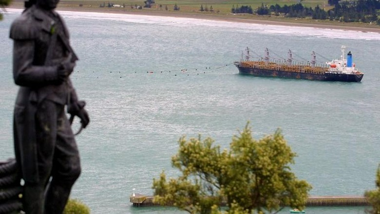 A statue of British explorer Captain James Cook overlooks the grounded South Korean log carrier Jody F Millennium at Gisborne on the North Island, 13 February 2002 as fears mount that it may break up and spill 650 tonnes of heavy oil fuel.  Ocean-going tugs are preparing to pull the 156-metre Panamanian registered bulk carrier off the sand ahead of forecast severe weather conditions. The ship became stuck fast on the beach that acquired world-wide fame during Millennium celebrations, as Gisborne was the first city to see the light of the new century, after being battered by a storm and huge swells on 06 February.  AFP PHOTO/Dean TREML / AFP PHOTO / DEAN TREML