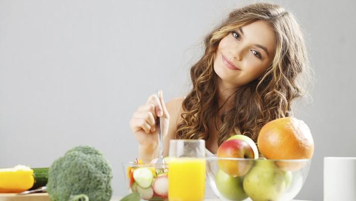 Remaja makan sayur dan buah