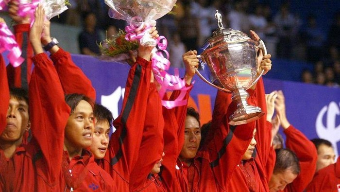 Indonesias badminton team celebrate with the Thomas Cup after beating Malaysia in the Thomas Cup mens team badminton final in the southern Chinese city of Guangzhou 19 May 2002.  Indonesia beat Malaysia 3-2 to defend the title as the world best mens badminton team .                      AFP PHOTO/GOH Chai Hin / AFP PHOTO