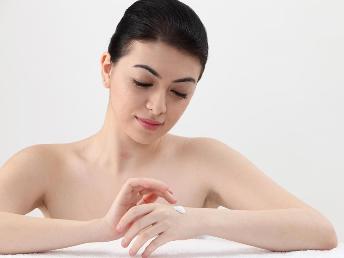 Young beautiful girl applying lotion with eyes closed