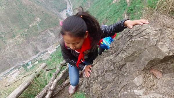 Anak-anak sekolah ini harus memanjat tebing terjal setinggi 800 meter, untuk mencapai sekolah mereka. Desa Atuleer yang penduduknya tidak lebih dari 400 jiwa ini menarik perhatian publik setelah media nasional Beijing News merilis foto-foto mengejutkan (Foto: Beijing News/Chen Jie)