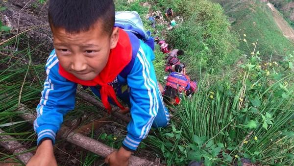 Pada tahun 2016, demi pergi ke sekolah, anak-anak di Provinsi Sichuan, China ini nekat bertaruh nyawa. Karena perjalanan yang sulit, anak-anak ini hanya pulang ke rumah dua kali dalam sebulan. Namun tetap saja, mereka harus menempuh perjalanan panjang selama 2 jam (Foto: Beijing News/Chen Jie)