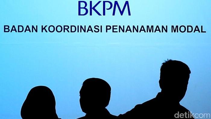 Siluet pegawai dan tamu di depan logo Badan Koordinasi Penanaman Modal (BKPM)