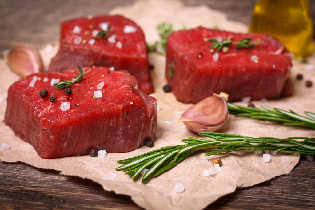 Raw beef steak with rosemary, thyme and garlic on wooden background