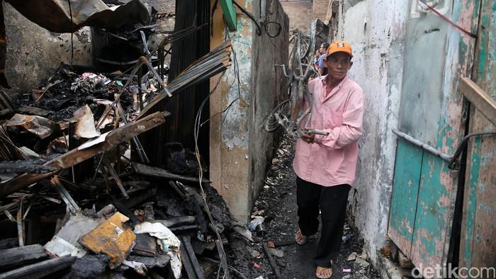 Pemulung barang bekas memunguti sisa perabot rumah tangga di lokasi kebakaran, di RT 12/10, Keagungan, Tamansari, Jakarta Barat, Selasa (14/6/2016) yang terjadi saat warga menyiapkan menu sahur Selasa dini hari.