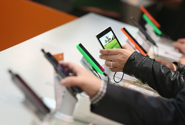 HANOVER, GERMANY - MARCH 16:  Visitors look at Windows-enabled smartphones, including the Nokia Lumia series, at the Microsoft stand the 2015 CeBIT technology trade fair on March 16, 2015 in Hanover, Germany. China is this years CeBIT partner. CeBIT is the worlds largest tech fair and will be open from March 16 through March 20.  (Photo by Sean Gallup/Getty Images)