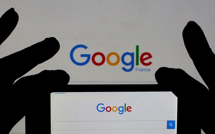 A woman holds her smart phone which displays the Google home page, in this picture illustration taken February 24, 2016. A U.S. Jury handed Google a major victory May 26, 2016 in a long-running copyright battle with Oracle Corp over Android software to run most of the worlds smartphones.  REUTERS/Eric Gaillard/Illustration/Files     TPX IMAGES OF THE DAY