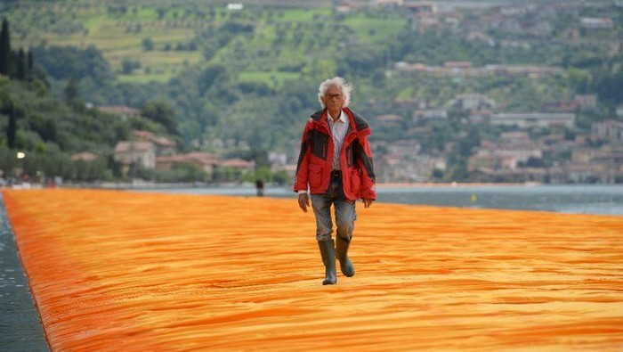 People walk on the monumental installation entitled The Floating Piers created by artist Christo Vladimirov Javacheff on Iseo Lake, in northern Italy, on June 18, 2016.