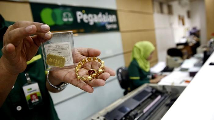 Seorang petugas menunjukan emas yang digadaikan oleh nasabah di kantor Pegadaian Pusat, Jakarta, Selasa (28/6/2016). Gadai emas menjadi pilihan warga untuk memenuhi kebutuhan jelang lebaran. Transaksi di Pegadaian pun meningkat dibanding bulan-bulan sebelumnya.