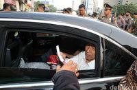 Jokowi saat bagikan buku dari dalam mobil kepresidenan