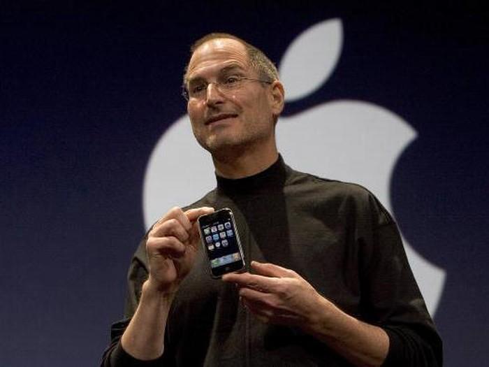 Steve Jobs memegang iPhone generasi pertama. Foto: Getty Images
