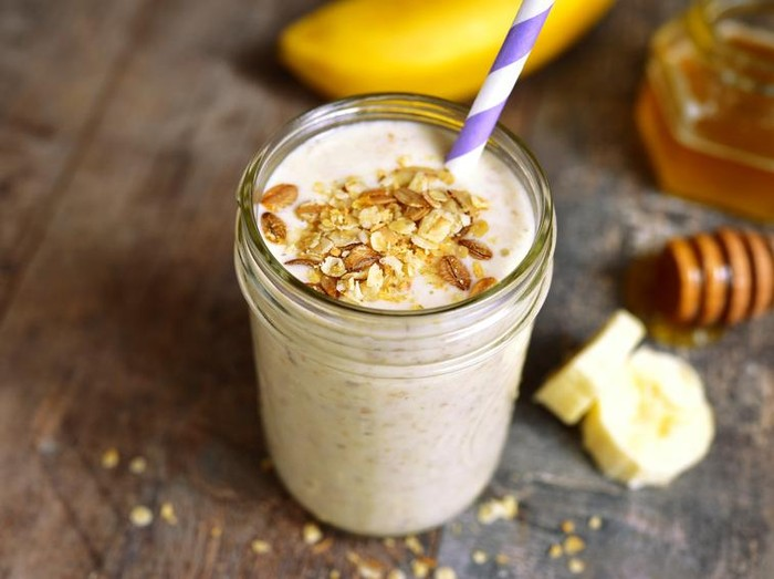 Banana smoothie with oat in a jar on rustic wooden background.