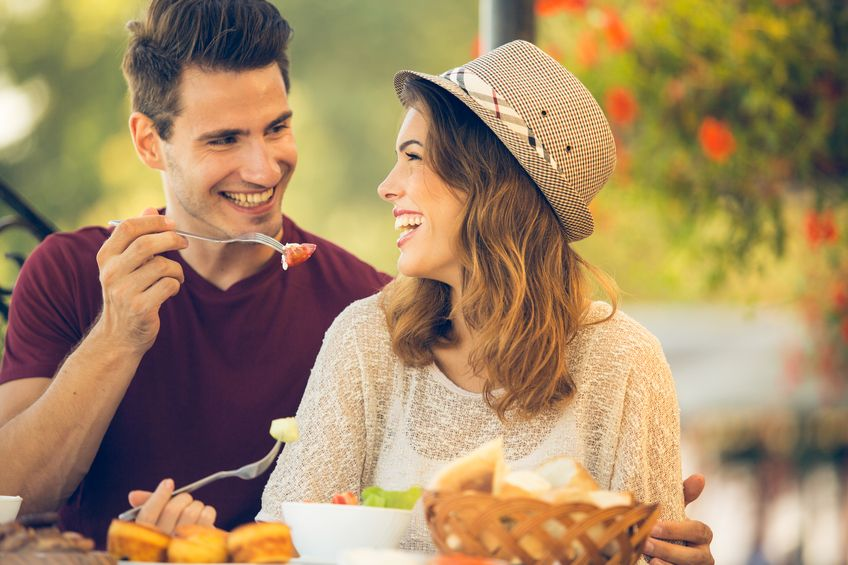 Photo of romantic dinner in expensive hotel. Young couple smiling while having dinner. Girl treating and feeding her boyfriend with salad