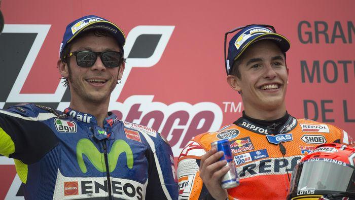 Valentino Rossi dan Marc Marquez berjabat tangan di podium MotoGP Argentina beberapa waktu lalu. (Foto: Mirco Lazzari gp/Getty Images)