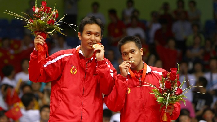 BEIJING - AUGUST 16:  Hendra Setiawan (L) and Markis Kido of Indonesia bite their gold medals in the mens doubles badminton gold medal match at the Beijing University of Technology Gymnasium on Day 8 of the Beijing 2008 Olympic Games on August 16, 2008 in Beijing, China.  (Photo by Lars Baron/Getty Images)