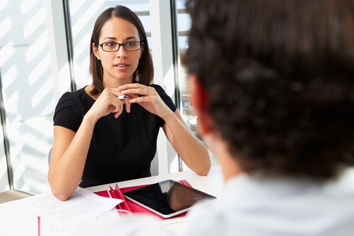 Businesswoman Interviewing Male Candidate For Job Holding Pen With Digital Tablet On Table