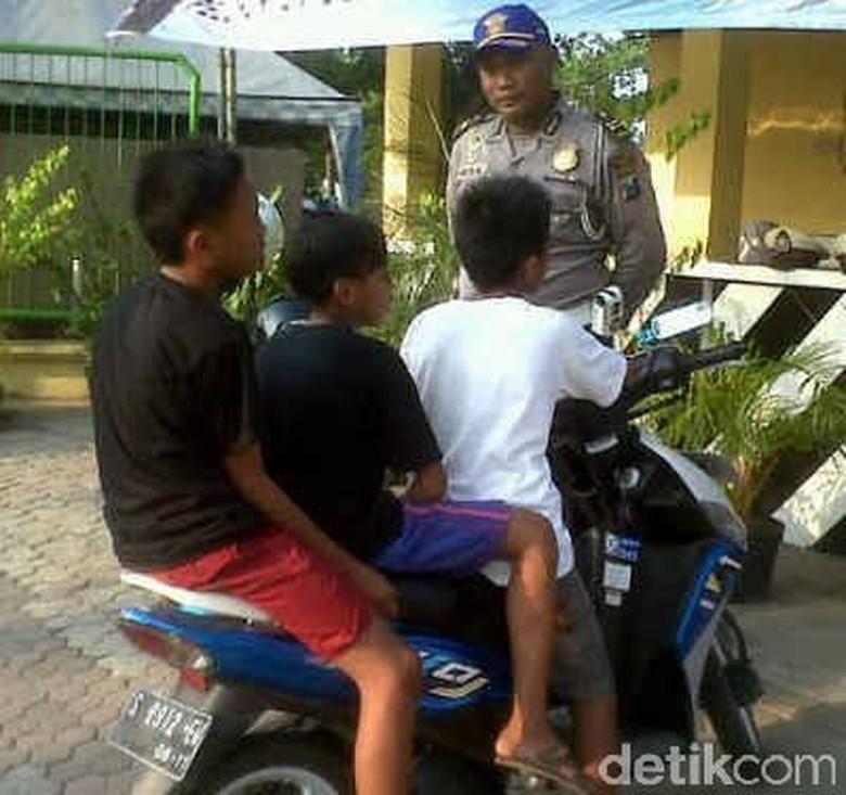 Polisi menghentikan anak yang naik motor (Foto: Dion Fajar)