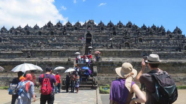 Turis berfoto sebelum menaiki tangga Borobudur (Fitraya/detikTravel)