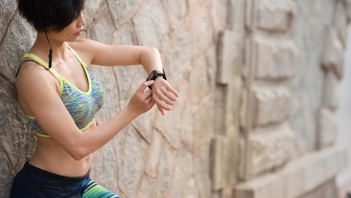 Woman checking activity tracker after outdoor training