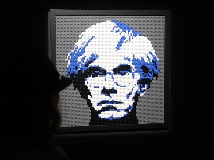 PARIS, FRANCE - MAY 15:  A visitor looks at a sculpture showing a portait of Andy Warhol made with Lego bricks by US artist Nathan Sawaya during the exhibition The Art of The Brick on May 15, 2015, in Paris, France. Nathan Sawayas exhibition takes place from May 14 to August 30, 2015.  (Photo by Thierry Chesnot/Getty Images)
