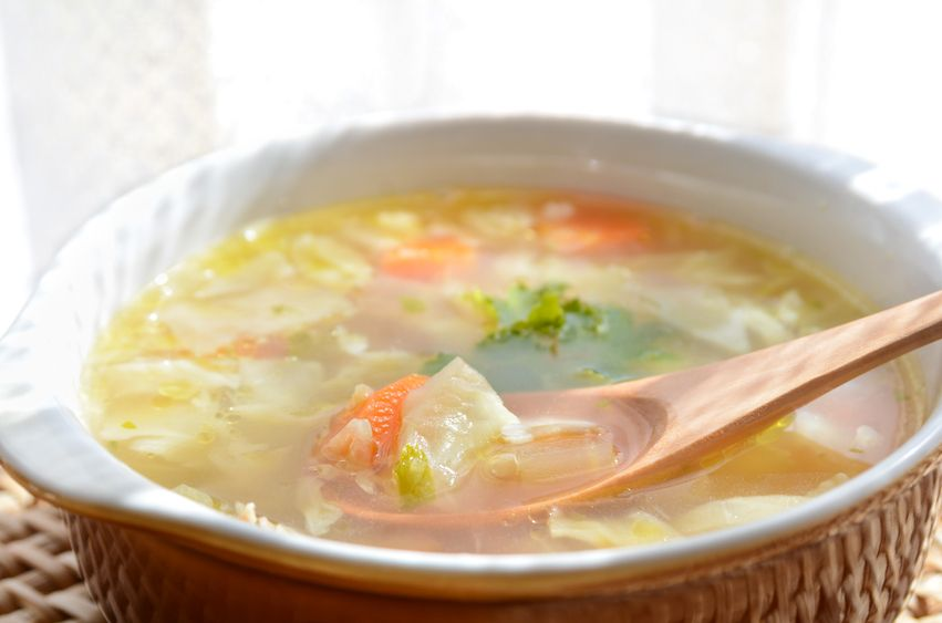 vegetable clear soup with wooden spoon on wooden table
