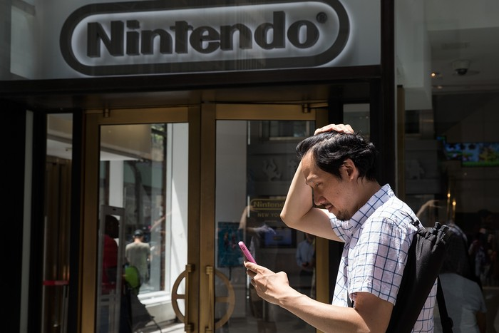 NEW YORK, NY - JULY 11: A man plays Pokemon Go on his smartphone outside of Nintendos flagship store, July 11, 2016 in New York City.  The success of Nintendos new smartphone game, Pokemon Go, has sent shares of Nintendo soaring. (Photo by Drew Angerer/Getty Images)
