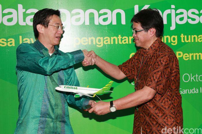 Direktur Produksi Citilink Indonesia Hadinoto Soedigno (kanan) menyerahkan miniatur pesawat kepada Direktur Retail Banking Permata Bank Bianto Surodjo (kiri).