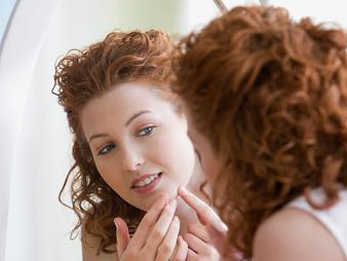 A young woman frowning in concentration as she squeezes a pimple