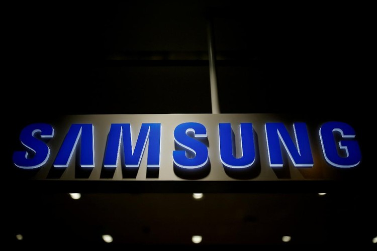 A man walks behind a logo of Samsung Electronics at the companys headquarters in Seoul April 30, 2010.  REUTERS/Jo Yong-Hak/File Photo