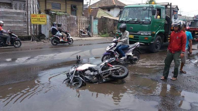 Ilustrasi motor jatuh di lubang jalan. Foto: Imam Wahyudiyanta