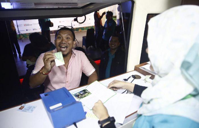 Mongol mendaftarkan diri di gerai mobil BPJS Ketenagakerjaan.