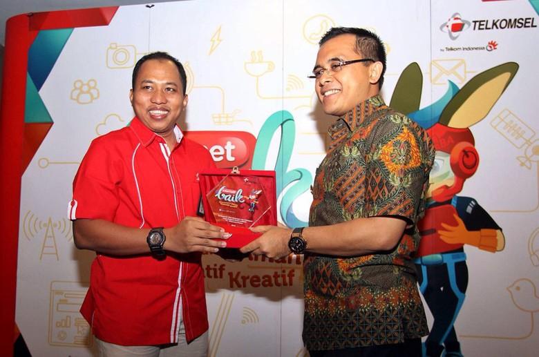 Manager CSR Environment and Ecosystem PT. Telkomsel Rifki Syabani (kiri) menyerahkan plakat internet baik Telkomsel kepada Bupati Banyuwangi Abdullah Azwar Anas (kanan). Ist/Telkomsel/.