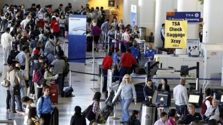 A TSA check baggage X-ray machine is seen in terminal 4 at LAX, Los Angeles International Airport, as travelers wait in a ticketing line in Los Angeles May 2, 2011. REUTERS/Danny Moloshok