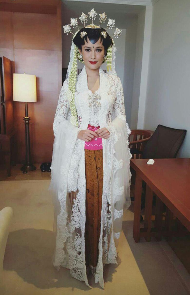 Titi nampak mengenakan kebaya berwarna putih dengan kain warna coklat. Penampilannya pun dilengkapi dengan hiasan kepala. Foto: Instagram bumiauw