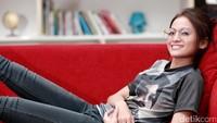 Aktris yang sebentar lagi akan menikah itu terlihat nyaman bersantai di sofa merah.