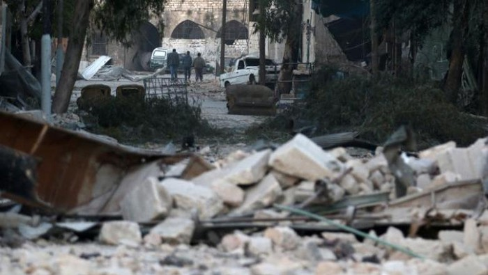 Orang-orang berjalan di dekat puing-puing bangunan yang rusak, di daerah terkepung dikuasai pemberontak Aleppo, Suriah