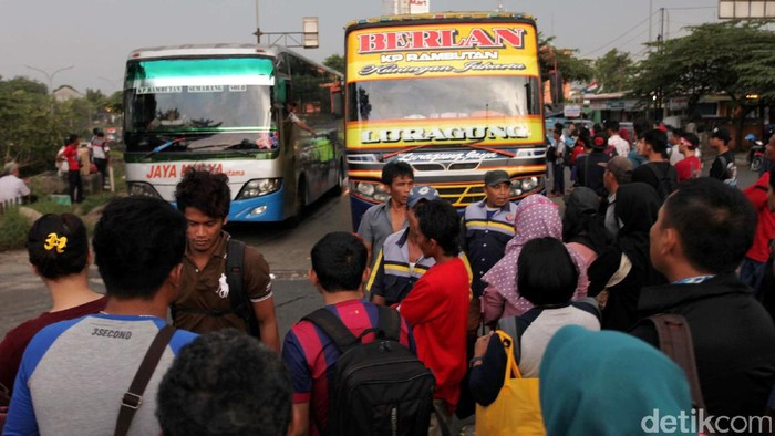 Libur panjang dimanfaatkan oleh warga untuk mudik. Seperti yang terlihat di pintu keluar Terminal Kampung Rambutan, banyak pemudik yang sedang menunggu bus.