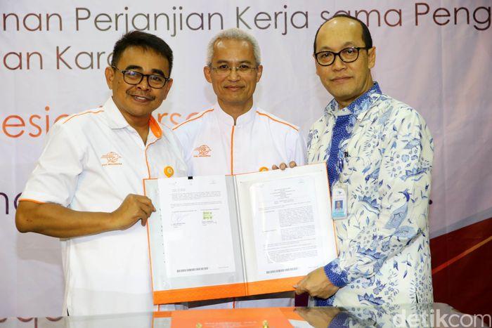 (Ki-ka) Direktur Surat dan Paket Pos Indonesia Agus F. Handoyo, Direktur Utama Pos Indonesia Gilarsi W. Setijono, dan Direktur Kargo Garuda lndonesia Sigit Muhartono menunjukkan naskah kerja sama.